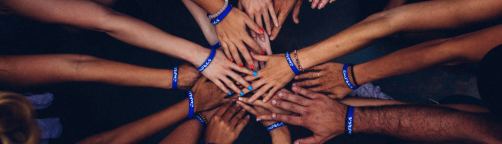 Banner image of team with hands together