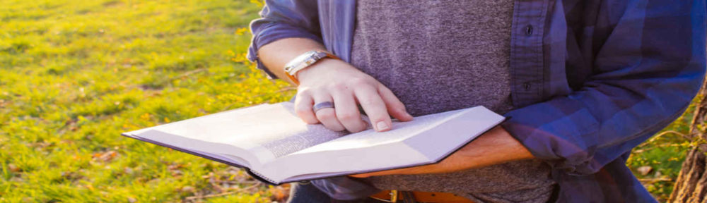 Civic header image of a man outside with bible.